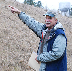 Portrait of David Gaylord pointing at something in the distance while doing fieldwork