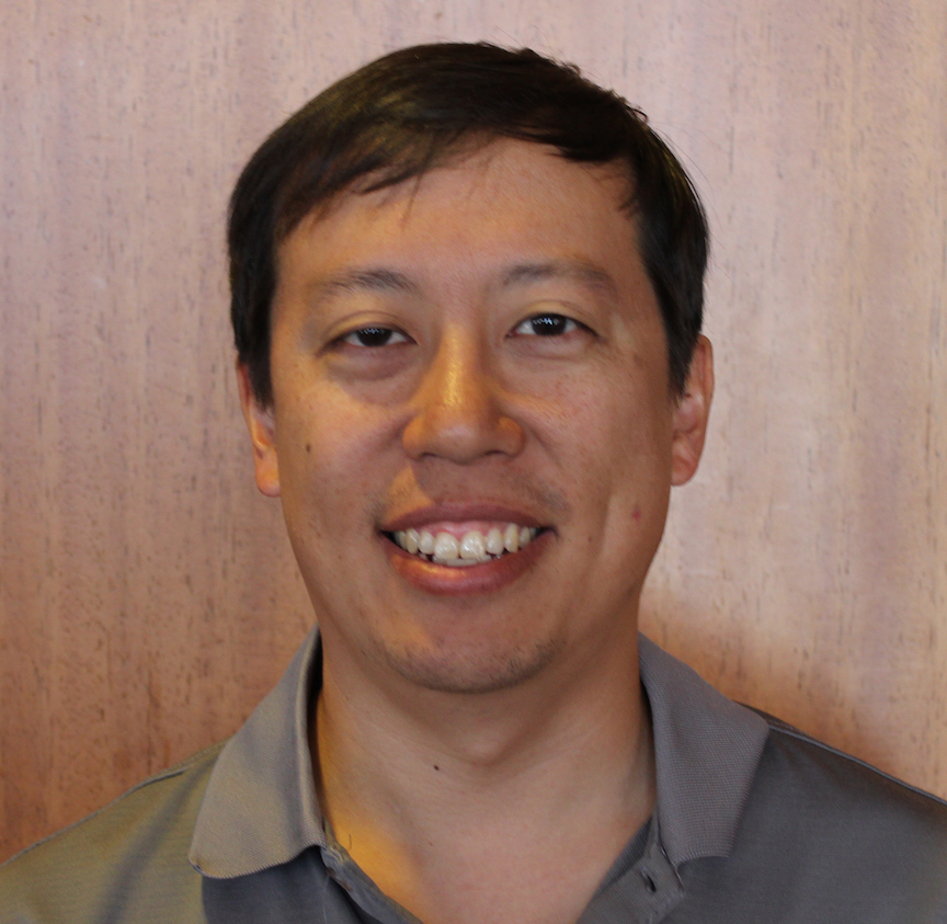 Portrait of Henry Hsieh, wearing a grey button-up shirt