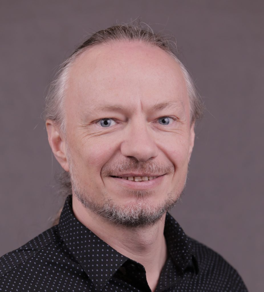 Portrait of Joern Helbert, wearing a black button-up shirt