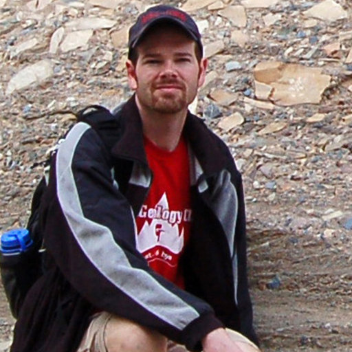Portrait of Mark Sweeny taken during field work. He's wearing a black jacket with white stripes on the sleeves over a red t-shirt.