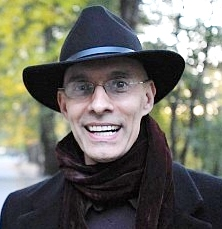 Portrait of Daniel Wolf Savin, wearing a black coat with a burgendy scarf and black wool felt hat